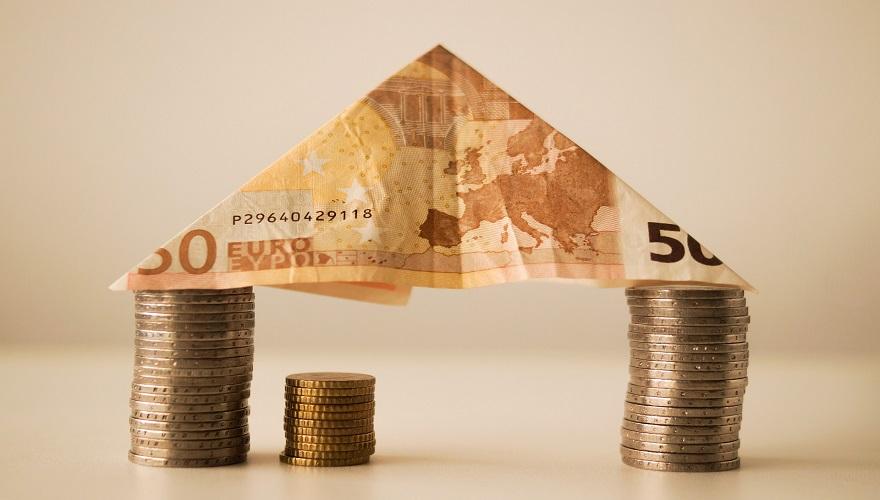 bankovka položená na stĺpcoch z mincí