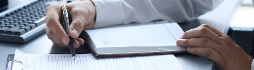 Ruka držiaca pero a zápisník